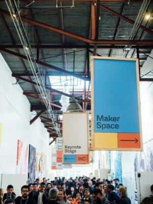 Foto einer Veranstaltungshalle mit Menschenmasse im unteren Teil und großen Schildern im oberen Teil des Fotos.