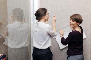 Photo von zwei denkmodell-Trainerinnen, die einen Workshop vorbereiten, indem sie ein Plakat an eine Wand hängen.
