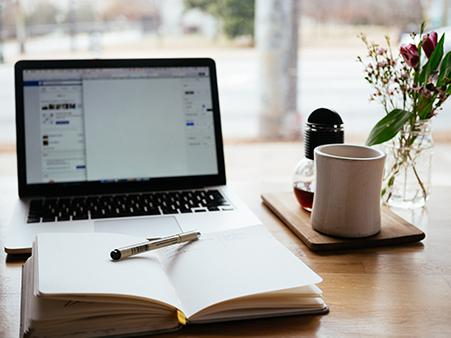 Foto eines Laptops mit Notizbuch, Stift, Tasse und Blumen im Gegenlicht.
