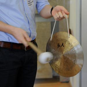 Angeschnittenes Foto einer Person, die mit einem Schlägel auf einen golenden Gong schlägt, den die Person in der Hand hält.