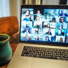 Foto mit einem Laptop wo ein Videochat zu sehen ist mit ganz vielen Teilnehmern