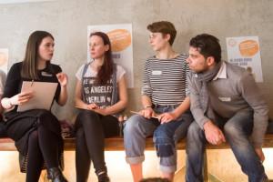 Photo von vier sitzendn Personen, die miteinander diskutieren.