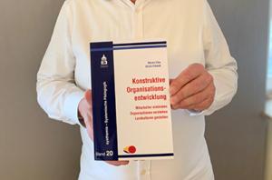 Photo wie denkmodell-Berater Urlich Erhardt sein Buch Konstruktive Organisationsentwicklung in Händen hält.