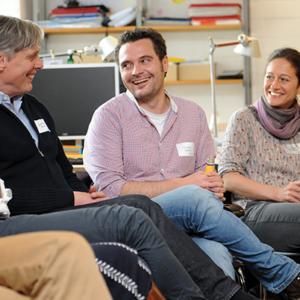 Drei Menschen sitzen zusammen und lachen, zwei Personen schauen dabei die andere Person an.