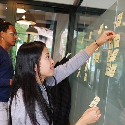 Photo von zwei Personen, die vor einer Milchglaswand stehen und gelbe Klebezettel darauf kleben als Symbolbild für Agile Methoden.