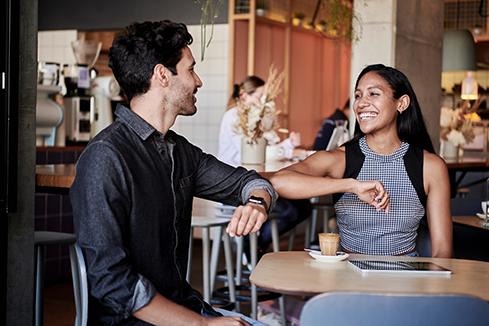 Photo von zwei Personen, die an einem Tisch sitzen, sich anlächeln und mit den Ellenbogen begrüßen.