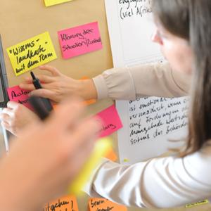 Foto einer Person im Hintergrund, die auf bute Klebezettel etwas an einer Pinnwand schreibt mit einem schwarzen Marker, eine unscharfe Hand mit Stift im Vordergrund als Symbolbild des Trainings Verhandeln nach HARVARD