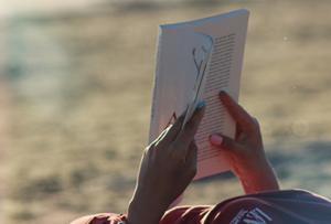Foto von zwei Händen, die am Strand ein Buch lesen als Symbolbild für Lesetipps.